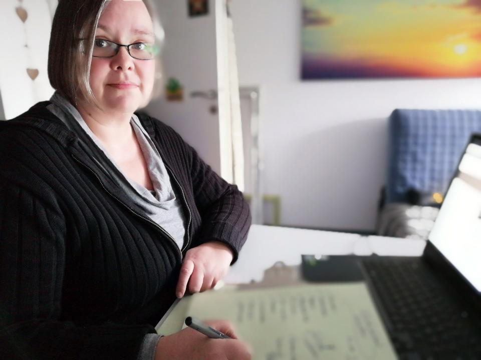 Nora Scheffler notiert Aufgabenlisten auf Papier und sitzt dabei vor dem Computer